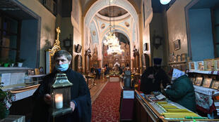 A Ukrainian Orthodox priest carries a candle with Holy Fire brought from Jerusalem in a church next to Kiev-Pechersk Lavra monastery in Kiev on April 18, 2020, on the eve of Orthodox Easter.