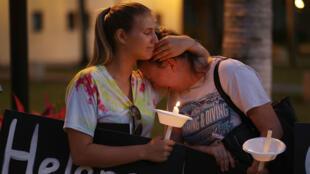 Tori Stetzer y Taylor Miller lucen conmovidas durante una vigilia con velas en la Universidad Atlántica de Florida para rendir tributo a las 17 personas asesinadas en el tiroteo del 16 de febrero de 2018.