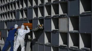 Los trabajadores del cementerio de Caju colocan el ataúd de una víctima de coronavirus, en Rio de Janeiro el 9 de mayo de 2020