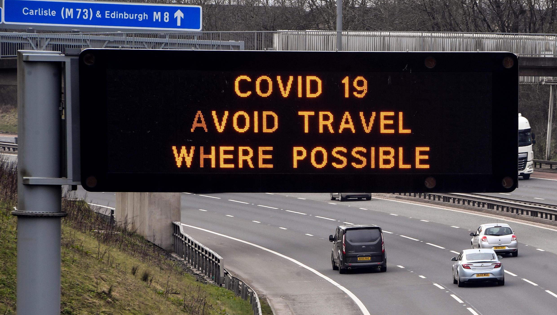 Sur cette autoroute de Glasgow, un panneau recommande d'éviter de voyager en raison du Covid-19, le 24 mars 2020.