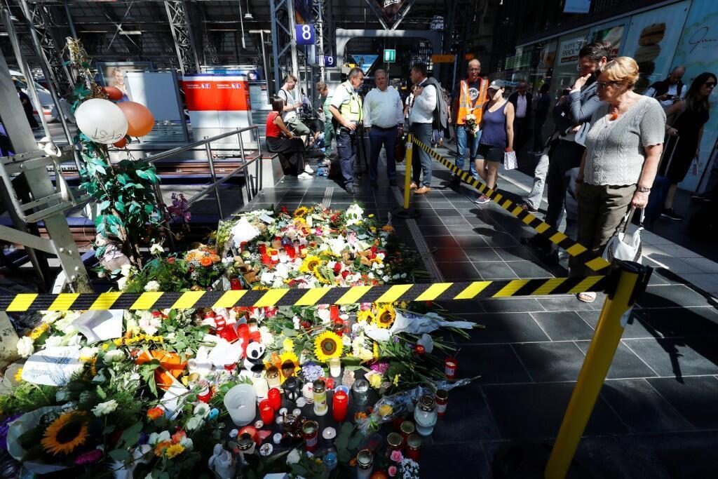 Decenas de personas dejaron arreglos florales el 30 de julio de 2019 en memoria del menor de ocho años que murió al ser arrojado por un desconocido a las vías del tren en Frankfurt, Alemania.