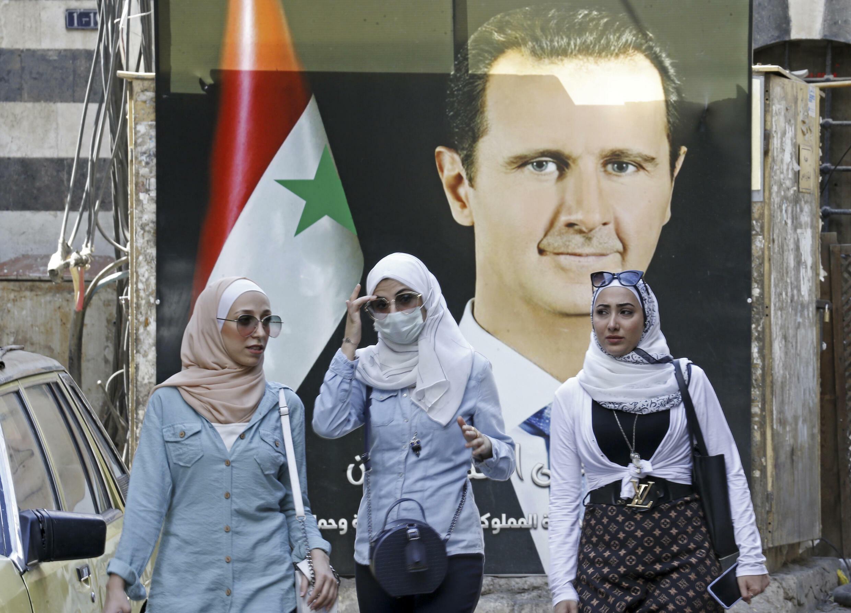 سوريات يسيرون أمام صورة الرئيس السوري بشار الأسد قرب الجامع الأموي الكبير في دمشق في 23 أيلول/سبتمبر 2021