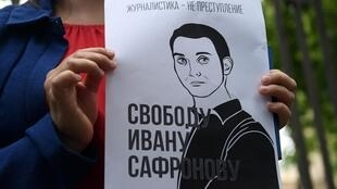 "A woman holds a poster featuring an image of Ivan Safronov and the words ""Journalism is not a crime"""
