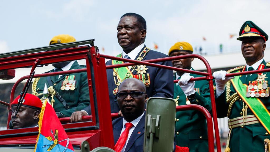 El presidente de Zimbabwe, Emmerson Mnangagwa (C) inspecciona la guardia de honor durante las celebraciones del Día de las Fuerzas de Defensa celebradas en el Estadio Nacional de Deportes en Harare el 14 de agosto de 2018.