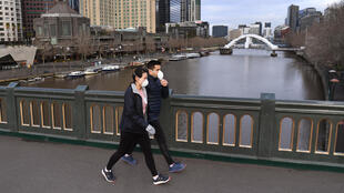 People wear masks as they cross Melbourne's Yarra River