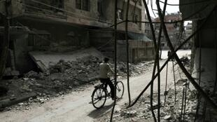 A Syrian rides his bicycle past a destroyed building in the Eastern Ghouta rebel-held enclave of Douma