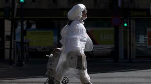 Una mujer con mascarilla y cubierta por un plástico camina por una calle de Granada, el 2 de mayo de 2020 en esa ciudad al sur de España