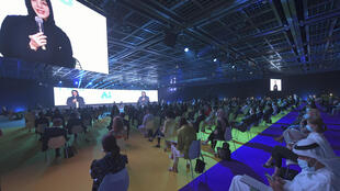 """The image of Reem Al-Hashimi, UAE Minister of State for International Cooperation, is projected on large screens as she speaks at the first post-lockdown """"real life"""" conference in the Gulf city of Dubai"""