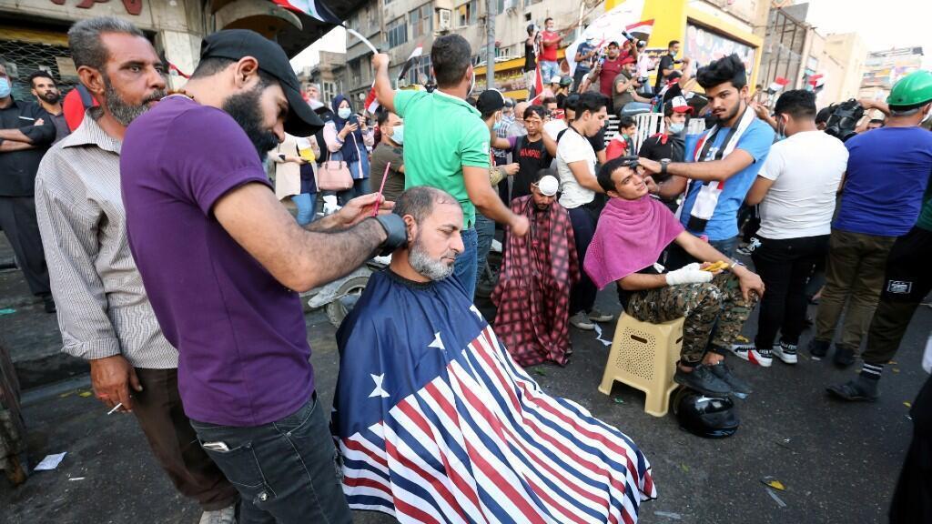 Los barberos iraquíes afeitan la cabeza de los manifestantes durante las protestas en curso en la plaza Tahrir, en el centro de Bagdad, Iraq, el 30 de octubre de 2019.