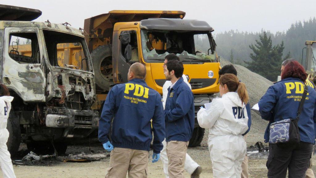 Los policías investigan la escena donde varios camiones fueron quemados por manifestantes en Los Alamos, Chile, el 16 de febrero de 2018.