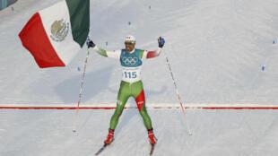 El esquiador mexicano Germán Madrazo cruza último la línea de meta elevando los brazos y ondeando la bandera de su país en la prueba de 15 kilómetros libres de esquí de fondo.