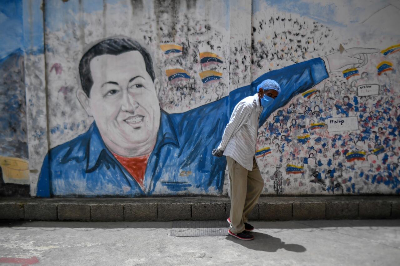 Un hombre con una mascarilla junto a un mural de Hugo Chávez en el Hospital Pérez de León del barrio de Petare, Caracas, el 23 de junio de 2020, en medio de la pandemia.