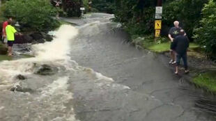 Habitantes de la localidad de Hilo en Hawái observan la crecida del río y cómo se inundó una de las carreteras del lugar el 24 de agosto de 2018.