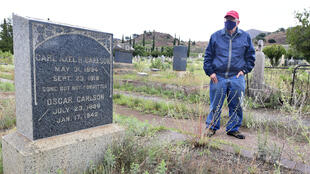 Historian and author Dave Anderson stands beside the grave of Army Private Carl Axel Carlson who died of the Spanish Flu in 1918