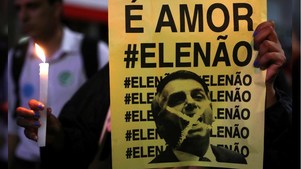"""En un acto en apoyo a Fernando Haddad, candidato presidencial del Partido de los Trabajadores, un manifestante sostiene una pancarta contra Jair Bolsonaro, candidato favorito en las encuestas que dice """"Es el amor, no él"""". Sao Paulo, Brasil, el 25 de octubre de 2018."""