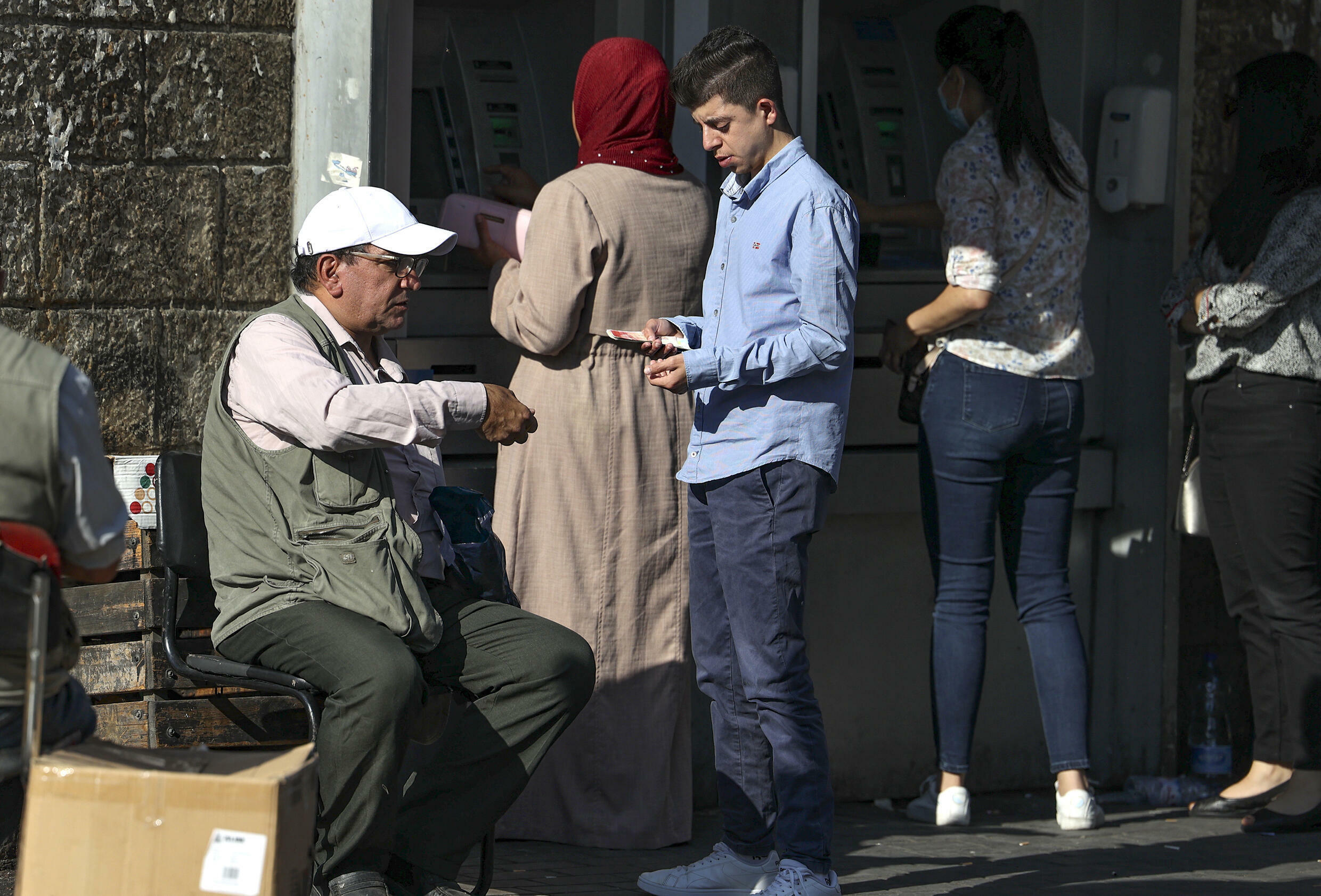 Palestinian men exchange currencies in the West Bank city of Ramallah; the local  shekel surplus has seen its value fall against major global currencies