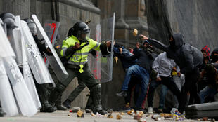 Un manifestante arroja una piedra a la policía antidisturbios durante una protesta, en Bogotá, Colombia, el 25 de abril de 2019.