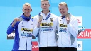L'Allemand Florian Wellbrock (c) médaille d'or du 10 km messieurs à Yeosi devant le Français Marc-Antoine Olivier et l'Allemand Rob Muffels le 16 juillet 2019