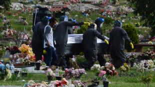 Los empleados de una funeraria llevan el ataúd que contiene los restos del periodista hondureño David Romero, durante su funeral en el cementerio San Miguel Arcangel en Tegucigalpa, el 18 de julio de 2020