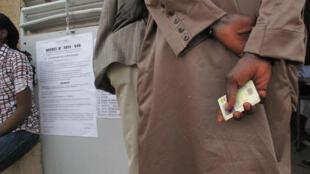 Une électeur sénégalais tenant sa carte électorale L, en 2012.
