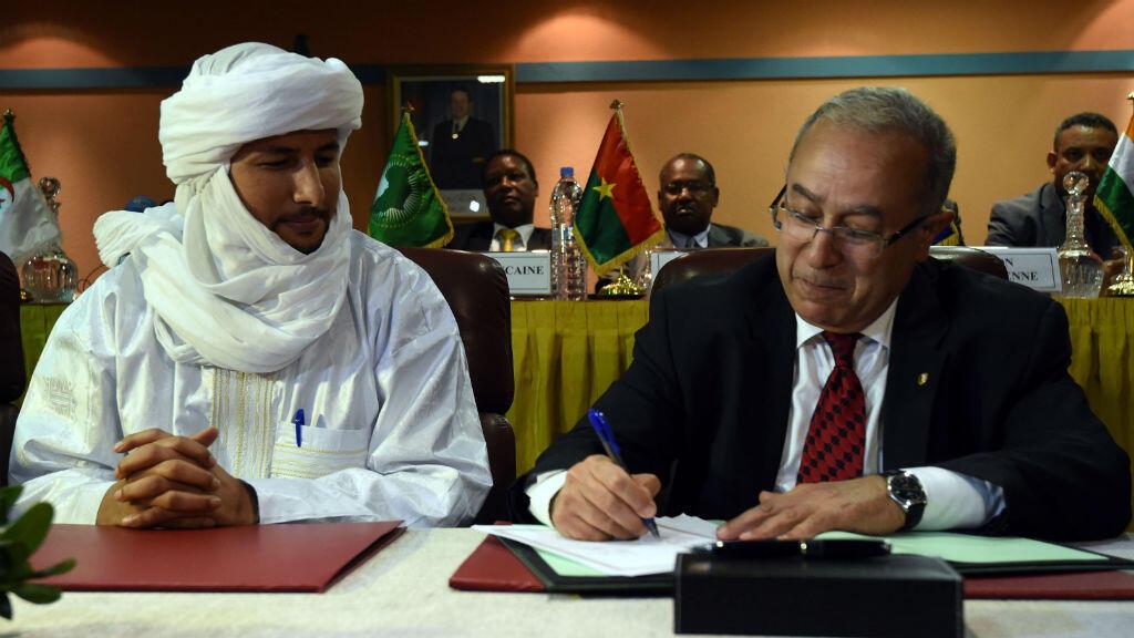 Le secrétaire général du MNLA et le ministre algérien des Affaires étrangères lors de la rédaction de documents préliminaires au traité de paix, le 19 février 2015 à Alger.