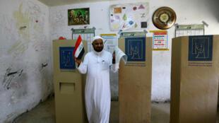 Un iraquí emite su voto en una mesa de votación durante las elecciones parlamentarias, en el distrito de la ciudad de Sadr, Bagdad, Irak, el 12 de mayo de 2018.