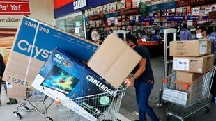Compradores salen de un almacén llevando electrodomésticos este viernes en Bogotá, Colombia. Miles de personas desafiaron el contagio del COVID-19 haciendo largas filas sin distanciamiento y aglomerados en almacenes durante el primer Día sin IVA, impuesto sobre el valor agregado, decretado por el gobierno nacional para reactivar el comercio durante la pandemia.