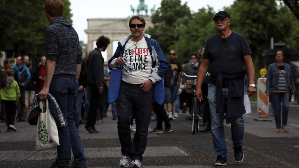 """La camisa de este manifestante dice """"no le den la oportunidad a (Bill) Gates"""", en alusión a las teorías que tienen algunas de las personas que protestan en contra del aislamiento en Berlín, Alemania, este 23 de mayo de 2020."""