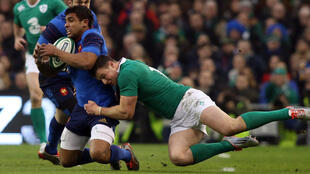 Ireland's centre Robbie Henshaw tackles France's centre Wesley Fofana.