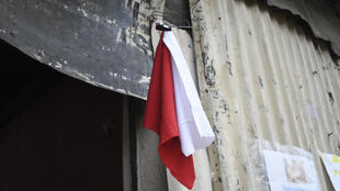 A woman hangs colored flags on the door of her house to signal she needs to be delivered food (white) and medicine (red) for her sick husband, at La Brigada neighbourhood in Guatemala City