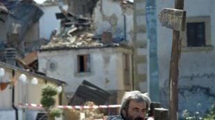 رجل يتأمل مبان في قرية توريتا التي دمرها الزلزال العنيف بمنطقة أمتريتشي وسط إيطاليا