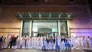 أطباء وممرضون إسبان أمام مستشفى ببرشلونة يصفقون تجاوبا مع مواطنين يفعلون الشيء نفسه امتنانا للعاملين في الحقل الطبي، 24 مارس/آذار 2020.