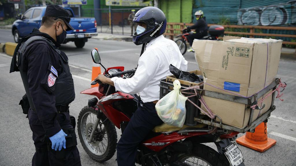 Un agente policial hace un control de tránsito a un motociclista en una avenida de San Salvador, El Salvador, el 7 de mayo de 2020.