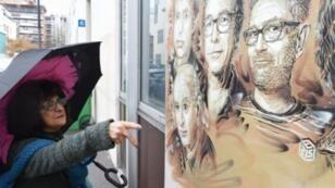 ليديا تشيلينكيريان تشير إلى غرافيتي فناني شارلي إيبدو المشوه بشارب هتلر بالقرب من المقر القديم للجريدة