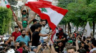 Des manifestants brandissent le drapeau libanais lors d'une manifestation contre la situation économique du pays, le 18 octobre 2019 à Sidon.