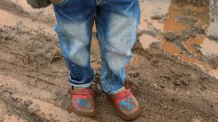 Un niño desplazado con zapatos embarrados se encuentra en un campo de refugiados en Quneitra, Siria, el 19 de enero de 2018.