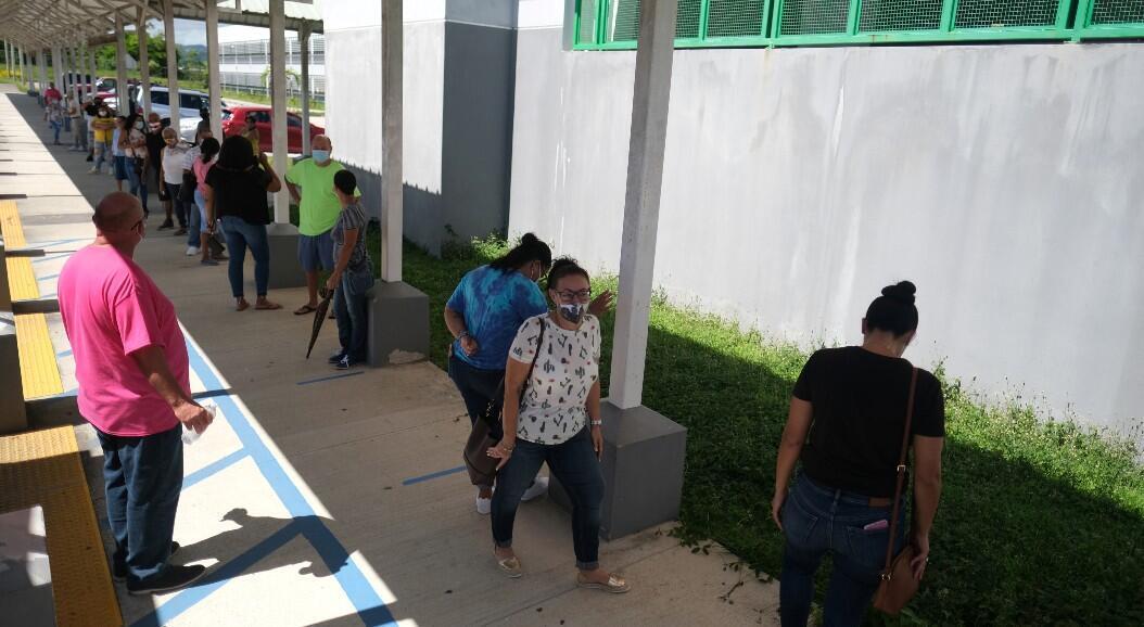 Decenas de personas esperan en fila para emitir su voto en las elecciones primarias, en Loiza, Puerto Rico, el 16 de agosto de 2020.