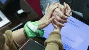 Una senadora que usa un pañuelo verde en la muñeca saluda a un senador durante la sesión para debatir el proyecto de ley sobre el aborto en Buenos Aires, Argentina, el 08 de agosto de 2018.