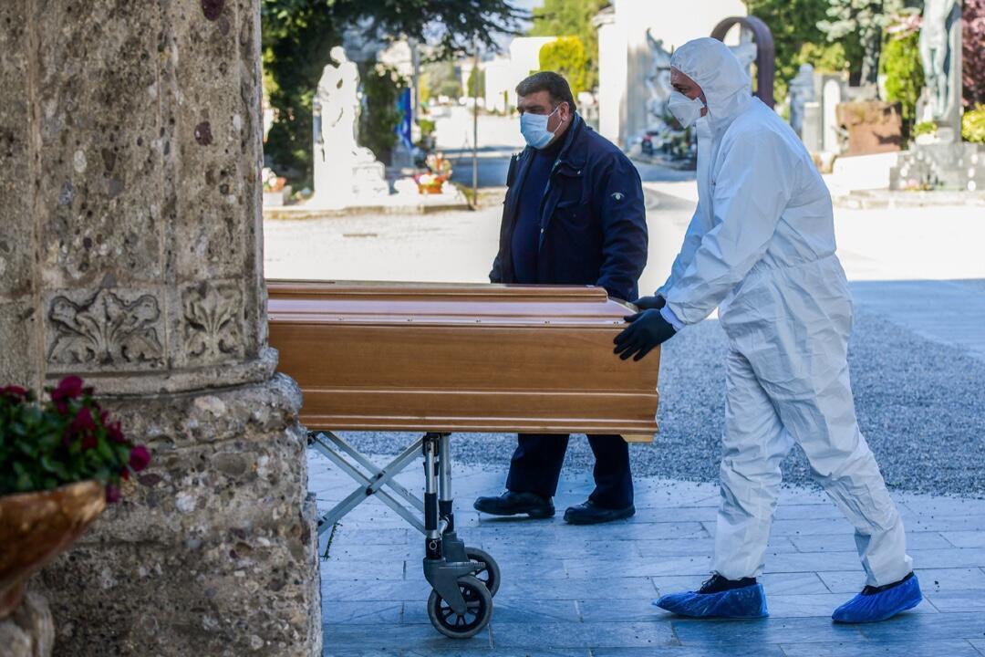 Dos integrantes de un equipo de atención fúnebre trasladan un ataúd el 16 de marzo de 2020 en el Cementerio de Bérgamo, Lombardía, en medio de la pandemia en Italia.