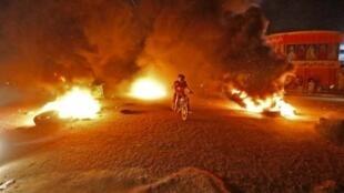 متظاهرون يحرقون إطارات خلال احتجاجات في مدينة البصرة ليل 12 تموز/يوليو 2018