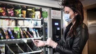 Una mujer con mascarilla y guantes compra en una máquina del metro de Moscú el 5 de mayo de 2020