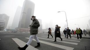Foto de archivo. Durante el smog en Beijing, un hombre usa una máscara de protección respiratoria mientras camina hacia un edificio de oficinas.