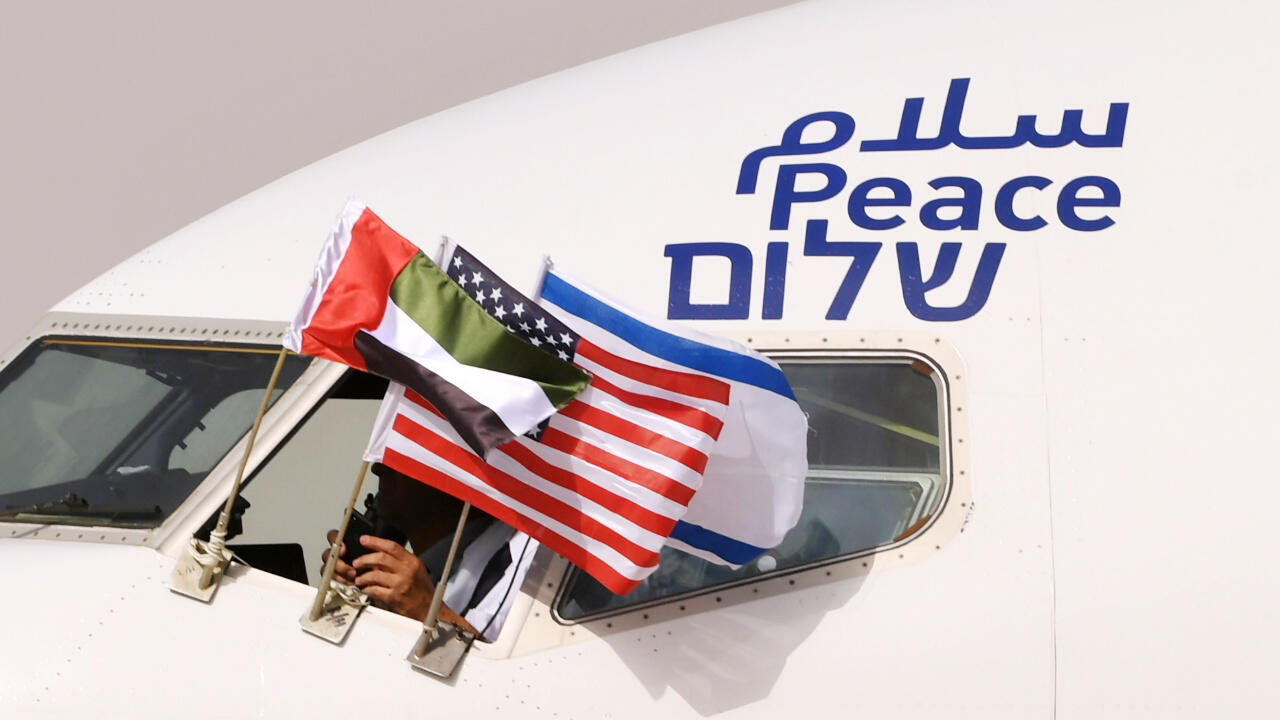 """The Emirati, Israeli and American flags attached to a plane of the Israeli company El Al, decorated with the word """"peace"""" in Arabic, English and Hebrew, on its arrival at Abu Dhabi airport on Israel's first ever commercial flight to the UAE, August 31 2020."""