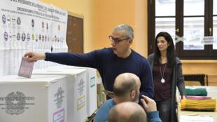 Un assesseur insère un bulletin de vote dans l'urne d'un bureau à Rome, le 4 mars 2018.