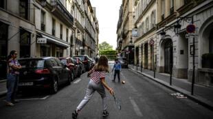 Des enfants jouant au tennis dans une rue de Paris pendant le confinement lié à la pandémie de coronavirus le 21 avril 2020.