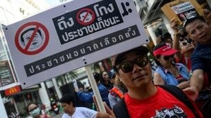 A Thai anti-junta protester displays a placard during a demonstration in Bangkok on Sunday