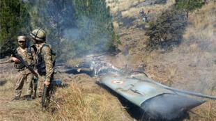 Los soldados pakistaníes ubicados al lado de lo que Pakistán afirma ser restos de un avión de combate indio que fue derribado en Cachemira en el área de Somani, distrito de Bhimbar, cerca de la Línea de Control, el 27 de febrero de 2019.