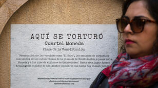 Una mujer se manifiesta este 10 de septiembre frente a un cartel que conmemora uno de los centros de tortura de la dictadura de Augusto Pinochet en Santiago de Chile