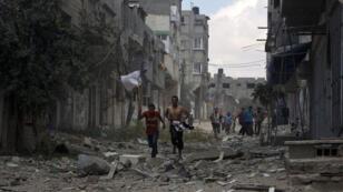 Des civils fuient le quartier de Chedjaïa, à Gaza, pilonné dimanche par des bombardements israéliens aériens.