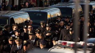 Des milliers de policiers se sont rassemblés autour d'une église du Queens samedi pour rendre hommage à leur collègue abattu le 20 décembre.